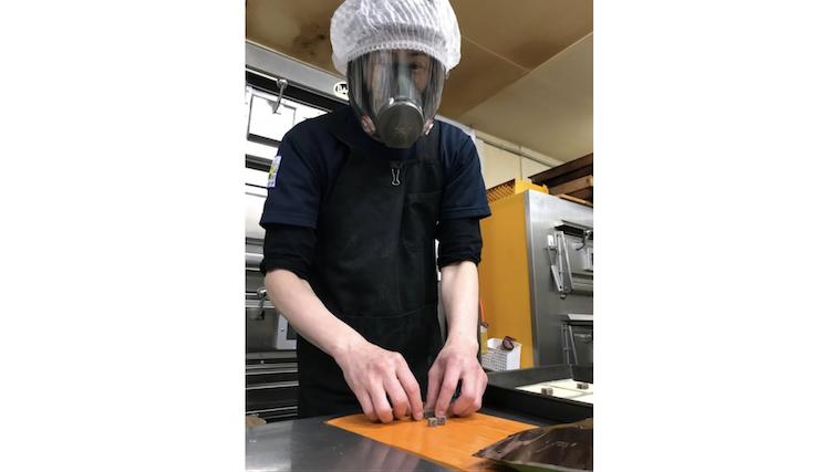 【写真】防護マスクをしてお菓子を製造するタカヨシさん