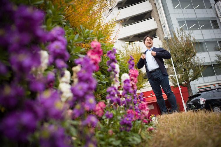 【写真】花壇の花の後ろに立ついしいさん