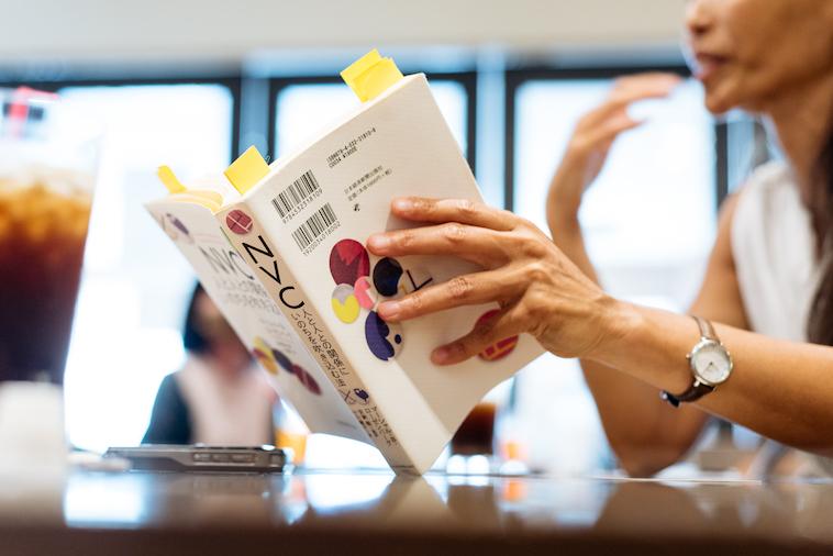 【写真】書籍『NVC 人と人との関係にいのちを吹き込む法』を眺めるここさん