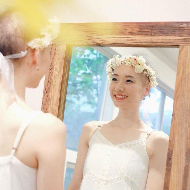 【写真】花冠をつけて笑顔で鏡を見ているめめさん
