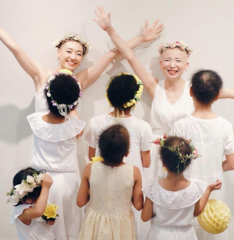 【写真】笑顔で花冠をつけている冠花の会のメンバーとmemeさん