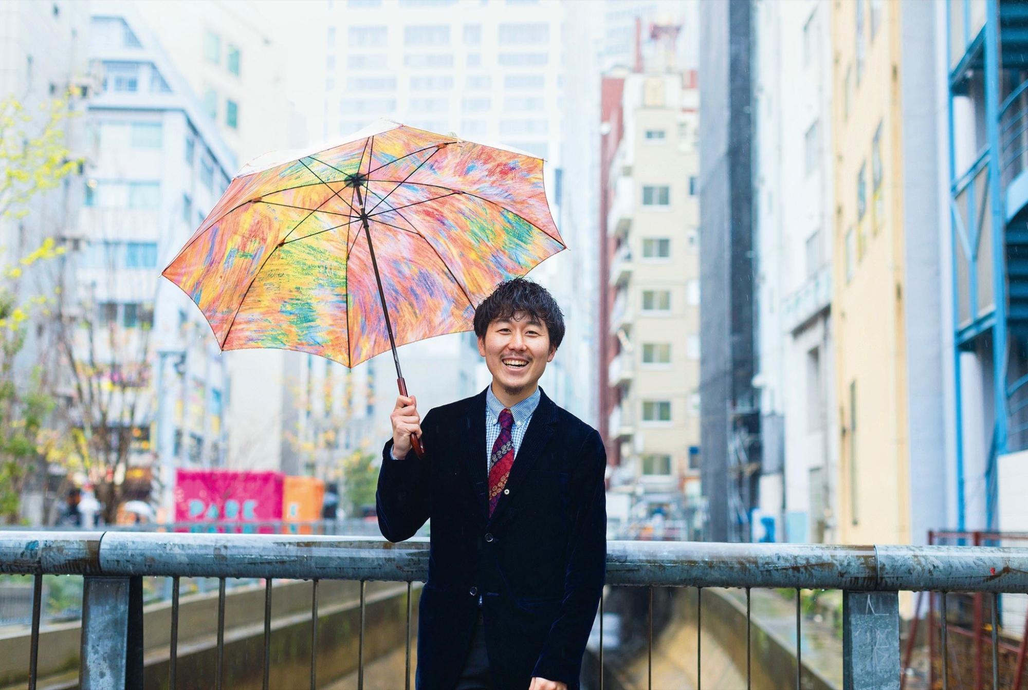 【写真】たくさんの色で装飾された傘を持って笑顔で立つ、ゲストの松田たかやさん