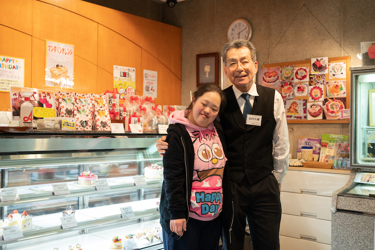 【写真】商店街の洋菓子屋さんのスタッフと肩を組むしょうこさん