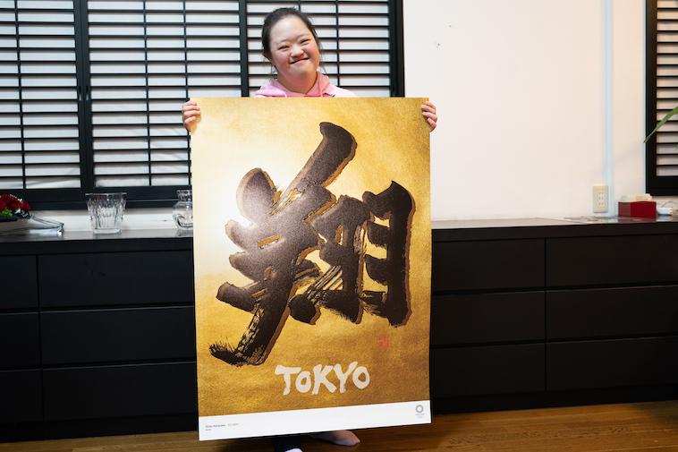 【写真】自身が描いた書を持っている翔子さん