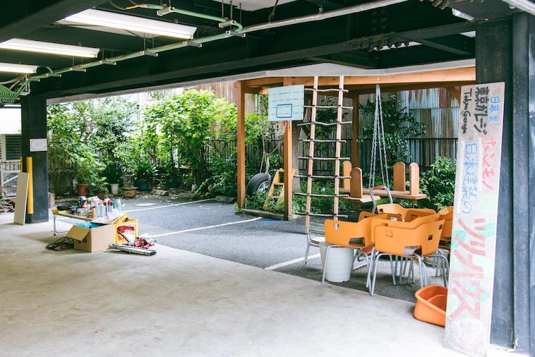 【写真】カラフルな看板、絵の具や木材が並ぶガレージ