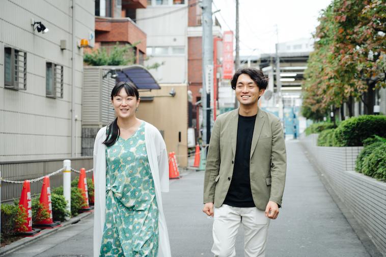 【写真】やすださんとすずきさんがはにかみながら歩いている様子
