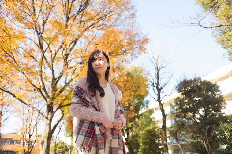 【写真】緑が広がる公園で遠くを見つめている秋本さん