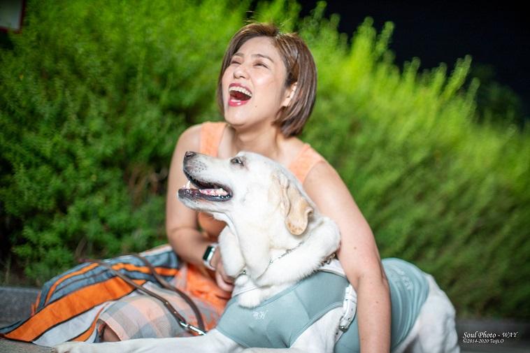 【写真】盲導犬のヴィヴィッドを抱きながら笑っているあさいさんと、それに応えるヴィヴィッド