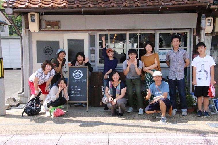 【写真】幸雲南塾の活動写真。拠点の前でカメラに笑顔を向ける参加者の方々