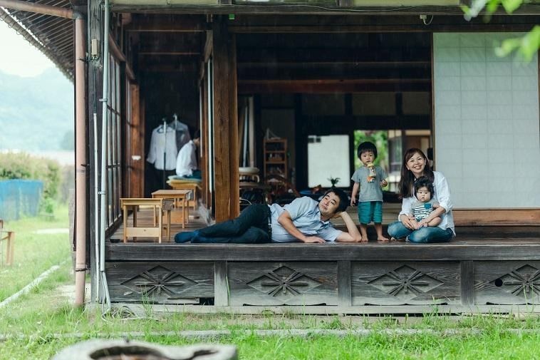 【写真】みんなのお家の縁側に座り子どもを遊ぶやたさん
