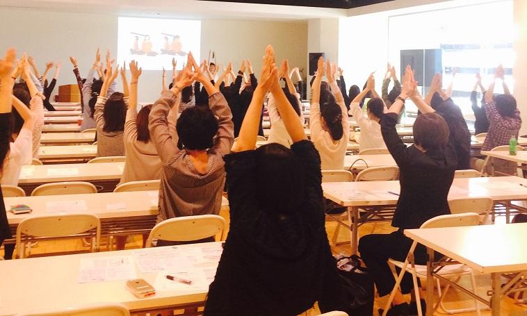 講座にてたくさんの参加者に体操を教えている様子。参加者は手を上に上げている