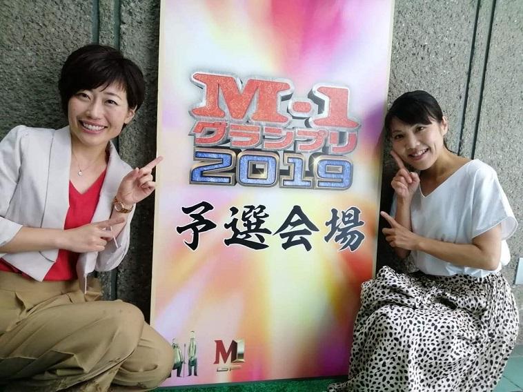 M-1グランプリ2019と書かれた看板の前で笑顔を見せるながたさん