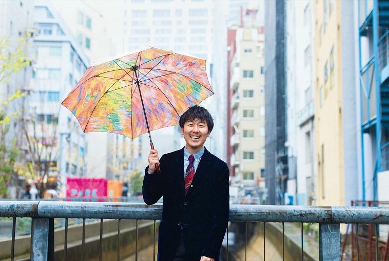 【写真】アート作品をモチーフにした傘を持ち、笑顔でこちらを見ているまつださん